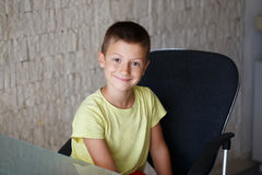 Happy little boy sit at glass desk in office Stock Photos