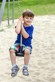Happy little boy sit on swing rope Stock Photos