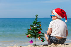 Happy little boy sitting on the beach at the day time. Stock Photos