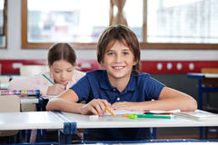 Happy Little Boy Sitting At Desk Royalty Free Stock Photos