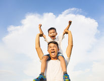 Happy little boy sitting on father's shoulder royalty free stock photos