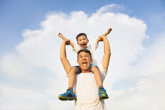 Happy little boy  sitting on father's shoulder Stock Images