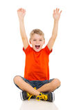 Happy little boy. Sitting on floor and arms up Royalty Free Stock Photos