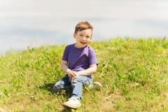 Happy little boy sitting on grass outdoors Stock Photo