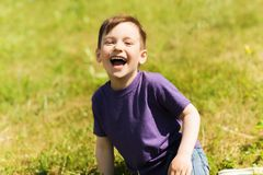 Happy little boy sitting on grass outdoors Royalty Free Stock Images