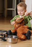 Happy little boy sitting on the kitchen floor playing with pots Stock Photos