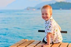 Happy little boy sitting on a pier Stock Photo