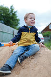 Happy little boy sitting on sand hill Royalty Free Stock Photography