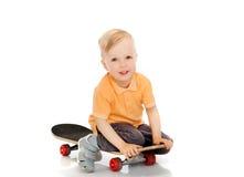 Happy little boy sitting on skateboard Stock Photography