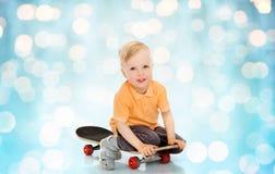 Happy little boy sitting on skateboard Stock Images