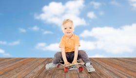 Happy little boy sitting on skateboard Royalty Free Stock Photography