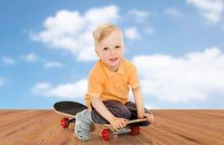 Happy little boy sitting on skateboard Royalty Free Stock Photos