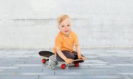 Happy little boy sitting on skateboard Royalty Free Stock Image