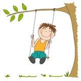 Happy little boy sitting on swing, swinging under the tree Royalty Free Stock Image