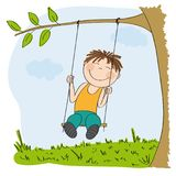 Happy little boy sitting on swing, swinging under the tree Royalty Free Stock Photography