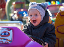 Happy little boy sitting in toy car. With open mouth Stock Photos
