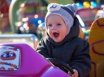 Happy little boy sitting in toy car Stock Photos