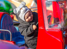 Happy little boy sitting in toy fire-engine Royalty Free Stock Photos