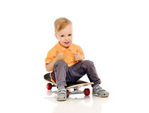 Happy little boy on skateboard showing thumbs up Royalty Free Stock Image