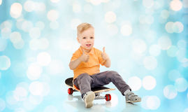 Happy little boy on skateboard showing thumbs up Royalty Free Stock Photo