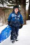 Happy little boy with a sled. Five year old boy outdoors in winter tobogganing Stock Images