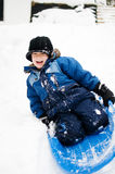 Happy little boy with a sled. Five year old boy outdoors in winter tobogganing Royalty Free Stock Photos