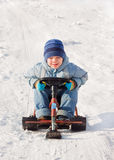 Happy little boy sledging at sleig. Happy little boy for a walk in a winter park,  sledging at sleig Royalty Free Stock Photography