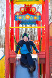 Happy little boy on a slide Stock Image