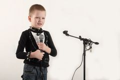 Happy little boy in smart clothes is singing a song with a microphone at home. Preparing for the Christmas Karaoke.  Stock Image
