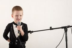 Happy little boy in smart clothes is singing a song with a microphone at home. Preparing for the Christmas Karaoke.  royalty free stock photos