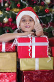 Happy little boy smiling with gift box near the Christmas tree Royalty Free Stock Photography