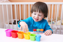 Happy little boy sorts details by color Stock Photography