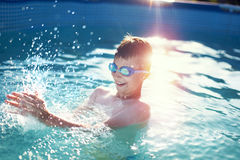 Happy little boy splashing in swimming pool Stock Images