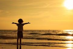 Happy little boy standing on the beach Stock Photo