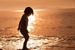 Happy little boy standing on the beach Stock Images