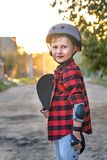 Happy little boy standing on the road holding a skate with his hands. the child defended himself, he put on hand safety gloves stock images