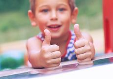 Happy little boy in a straped t-shirt shows the OK gesture at the playground. Smiling little boy in a straped t-shirt shows the OK gesture at the playground stock image