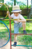 Happy little boy in straw hat on climber outdoors in summer Royalty Free Stock Image