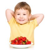 Happy little boy with strawberries Stock Photography