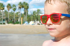 Happy little boy sunbathing in the summer wearing sunglasses Stock Photography