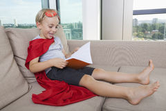 Happy little boy in superhero costume reading book on sofa at home Royalty Free Stock Image