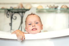 Happy little boy swimming in the bathroom. Portrait of baby bathing in a bath full of foam royalty free stock images