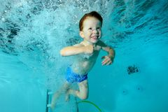 Happy little boy swimming and playing underwater in pool in water jets on blue background and smiling. Portrait. Shooting under water. Horizontal view Stock Images