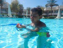 Boy swimming at pool with mask. Happy little boy swimming at pool with diving mask royalty free stock photography