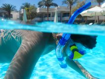 Boy swimming at pool with mask. Happy little boy swimming at pool with diving mask stock images