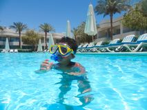 Boy swimming at pool with mask. Happy little boy swimming at pool with diving mask royalty free stock photo