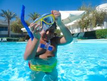 Boy swimming at pool with mask. Happy little boy swimming at pool with diving mask stock photos
