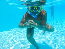 Boy swimming at pool with mask. Happy little boy swimming at pool with diving mask royalty free stock images