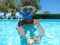 Boy swimming at pool with mask. Happy little boy swimming at pool with diving mask royalty free stock image