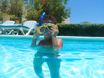 Boy swimming at pool with mask. Happy little boy swimming at pool with diving mask stock image